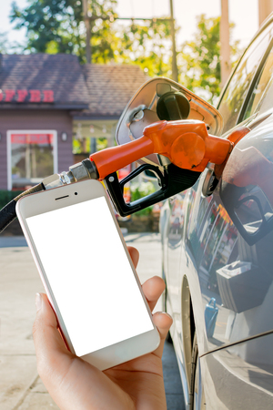 Women use mobile phone ,  image of car refueling on petrol station and fuel pump with gasoline  in the background.