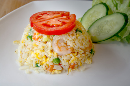 Fired rice with shrimp and vetgeable on whith dish. Stock Photo