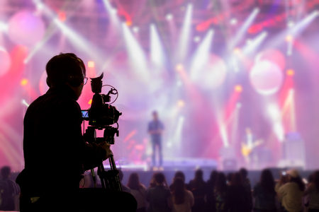 The filmmaker is recording and broadcasting live concerts on camcorders. Professional Video Recording Business Foto de archivo