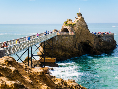 The metal bridge can be seen leading to the landmark Rocher de la Vierge, a statue of Virgin Mary on the rock formation at Biarritz, Basque Country Stock Photo
