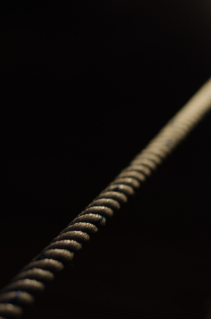straight rope on a black background is illuminated with light