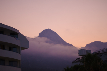 mountains at sunset with fog casts a pink color.