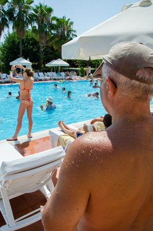 an elderly man with glasses and a cap looks at a young girl in the pool. Stockfoto