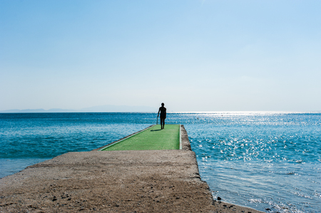 man goes to the green pier to dive. 写真素材
