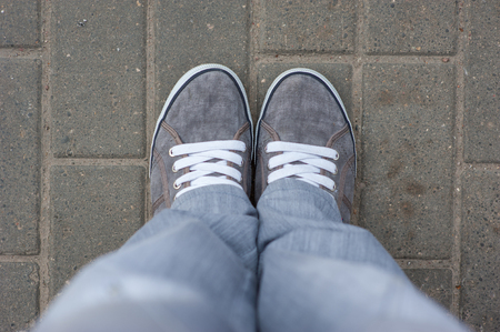 Gray sneakers with white laces stand on the tile, top view, comfortable shoes for walking around the city. gray bottom clothes. Stock Photo