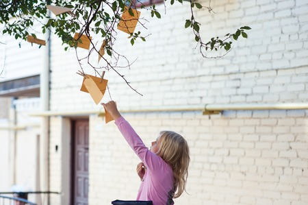 A girl tears a note from a tree, from a branch, disrupt desire.