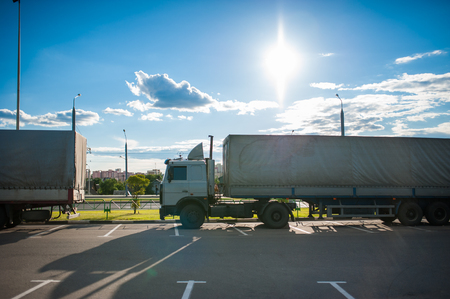 A white semi truck with a cargo trailer rides into the parking lot and parked with other vehicles. Wagons on unloading goods..