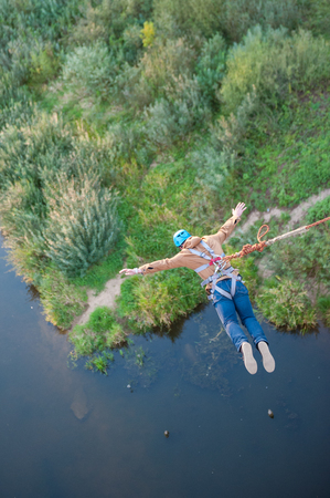 Extreme jump from the bridge. The man jumps surprisingly quickly in bungee jumping at Sky Park explores extreme fun. Bungee in the canyon