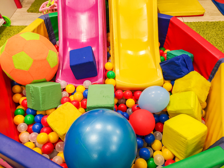 Playground, children's slides, a play area of colorful plastic balls. Cheerful children's leisure with balls in the play pool, on the playground