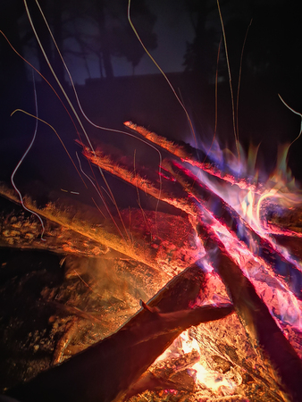 Extreme close up of fire sparks moving on dark night sky as black background coming from brightly burning warm outdoors bonfire in forest.