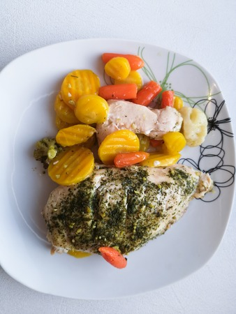 chicken breast with vegetables on a plate, dinner service, vegetarian food, healthy food. baked chicken breast with brussels sprouts, onions and carrots on a white plate on wooden surface. Healthy food