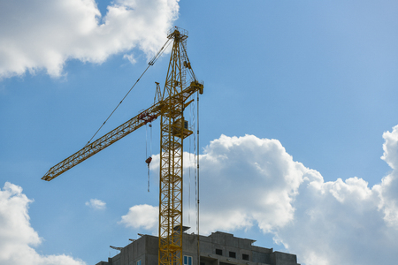 high-rise construction crane with a long arrow of yellow color against the blue sky over a new multi-storey building of concrete and brick under construction. Banque d'images
