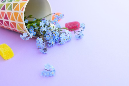 Flowers in a glass on a purple background. Fresh cut purple lilac flowers. colorful dishes, blooming flowers. Copy space.