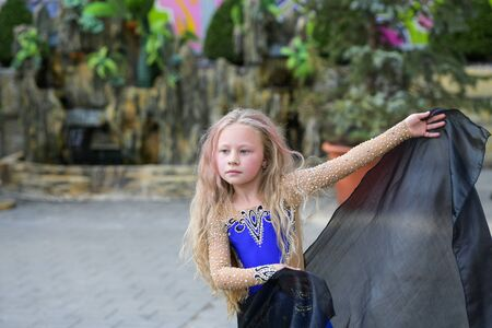 One beautiful young girl fits a modern dancer in a blue suit, a young dancer, dancing and jumping, Dance with a scarf. Young girl dancing in blue Standard-Bild - 132493848