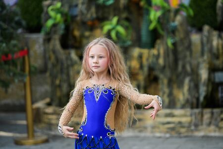 One beautiful young girl fits a modern dancer in a blue suit, a young dancer, dancing and jumping, Dance with a scarf Standard-Bild - 132493849