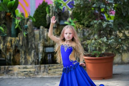 One beautiful young girl fits a modern dancer in a blue suit, a young dancer, dancing and jumping, Dance with a scarf. Young girl dancing in blue. Standard-Bild - 132493854