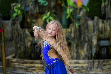 One beautiful young girl fits a modern dancer in a blue suit, a young dancer, dancing and jumping, Dance with a scarf. Young girl dancing in blue. Standard-Bild - 132493856
