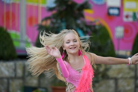A young girl in pink is dancing. Smiling dancing. Dancing in the street. In the costume dancing