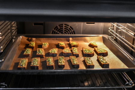 Black bread with cheese in the oven. Roasted bread with cheese and spices, cooked in the oven on a black tray, delicious breakfast Stock Photo