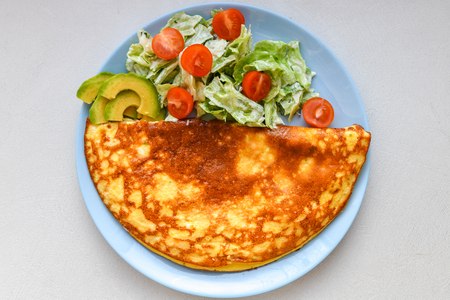 Fried eggs with vegetable salad. Omelet with vegetable salad..