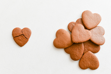 Galletas en forma de corazón, una de ellas está rota sobre un fondo blanco. Romper las galletas en forma de corazón como un concepto de relaciones fallidas, amor no correspondido. Concepto de amor no correspondido ... Tarjeta del día de San Valentín. Vista desde arriba.