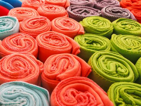 multi-colored towels rolled into a tube lie on each other on the shelf Stockfoto