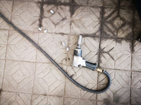 Pneumatic wrench with a long hose lying on the floor of stone tiles, top view.