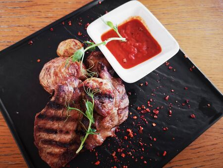 Fried meat with potatoes. fried pork with seasonings on a square plate with tomato sauce, on a wooden table. Standard-Bild