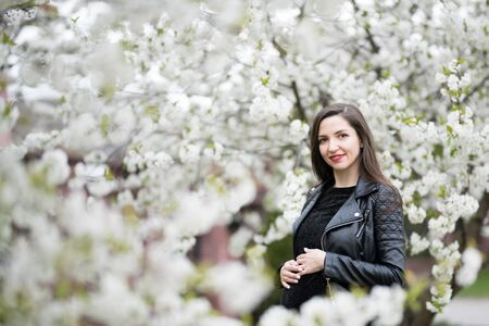 Pregnant brunette in the flowered park. The brunette in a dark dress poses in the blossoming apple orchard, the dress hiding pregnant. Archivio Fotografico