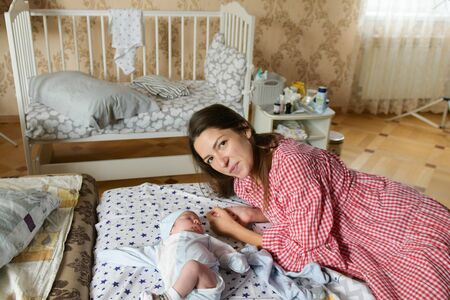 Happy mother with baby at home. Young mother holding her newborn baby. A woman and a newborn boy are resting in the bedroom with a white cot. Childrens room interior. Family at home. the joy of the m