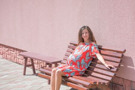 The pregnant girl basks in the sun. The concept of warm leisure - a beautiful pregnant girl with long hair, basking in a red dress. sitting on a bench. pink background. place for writing. 版權商用圖片