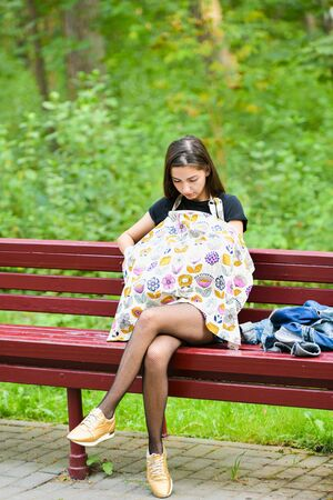 Mom feeds the newborn on the bench. covered with a diaper from prying eyes. Young woman, new mother breastfeeding and caring her cute baby with love and kindness, nursing newborn outside on daylight,
