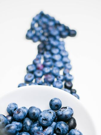 Blueberry Arrow. composition of fresh blueberry onions on a white background. pointer to vitamins, berries. Top view, flat lay. Stock Photo