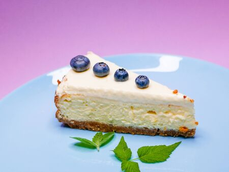 Blueberry Cheesecake. Blueberry mint cheesecake on a pink, purple, coral background. on a blue plate. Tasty breakfast. side view. Stock Photo - 128946414