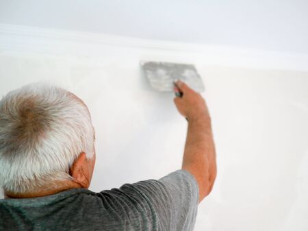 man with a spatula. gray-haired man makes repairs at home. alignment of walls. wholesale developer. back view. Man plastering wall with putty-knife, close up image. Fixing wall surface and preparation for painting