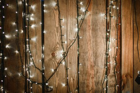 garlands on wooden background. Light bulb on wooden background ,Space for your task or message Фото со стока