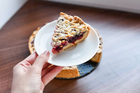 Pie with berries: raspberries, strawberries, currants, on a white plate,a womans hand holding a piece of cake on a spatula. On a wooden background, in the background linen napkin.