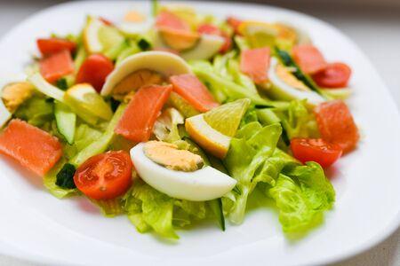 ensalada de verduras en un plato blanco. Ensalada fresca con huevo, tomates, espinacas y aguacate en una vista superior de fondo de madera blanca. Comida sana Foto de archivo