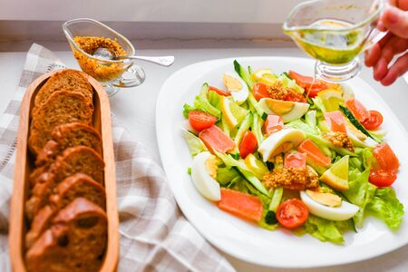 vegetable salad with bread and mustard. on a white plate. view from above.