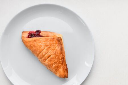 croissant on a white plate. Croissant on white plate, top view. Sweat baked dessert in a dis