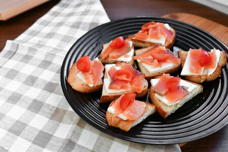 red salmon on white bread. bagel and lox. view from above. black plate on a white background.