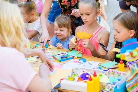 MOSCOW, RUSSIA - April 24, 2019: children and adults at the table do needlework and paint on the street on a sunny day. children's Day. developing club for children with disabilities