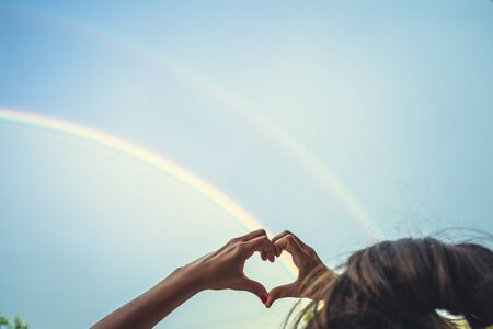 symbolism of love, rainbow sky, love. heart shaped hands and rainbow in the sky. double rainbow Imagens