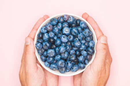 The usefulness of blueberries. Closeup of blueberry berries with hands in a light dish background. Photo of blueberries for designers on the banner. Useful berries for vision. love for berries.