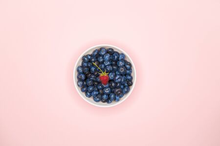 blueberries in a bowl. Blueberries on a colored background. place for writing. view from above. sprinkle in pasuda. natural berries. Top view of fresh ripe blueberries in a bowl.