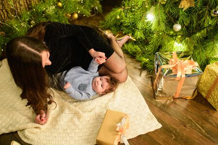 Mom and baby hug at the Christmas tree. Happy baby and his mom are looking at the frame. Mom with son hugging for Christmas. and have fun. newborn baby for the new year.