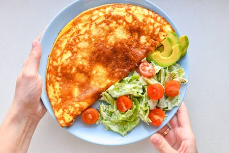 fried eggs with vegetables. hands in the frame. Vegetable omelet on a blue plate on a white table, top view. Stock Photo