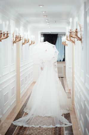 The bride with a white umbrella. Beautiful wedding woman or pretty sexy bride. A girl in a white dress holds a lace umbrella, standing with his back. walking along the white corridor. In a hotel. Honeymoon. hotel room for honeymooners. Stock Photo
