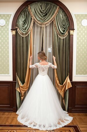 Girl in a white wedding dress by the window. Against the background of the window is a beautiful woman in a white wedding dress with beautiful make-up and hairstyle. opening the window curtains. Standing back beautiful interior