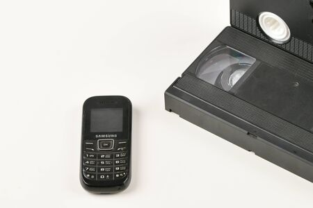 Retro objects on a white background. push-button telephone and video cassette. Analog media technology of the past. Copy space.
